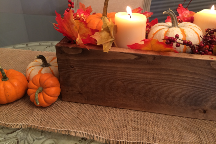 Close up of fall centerpiece box with candles and pumpkins