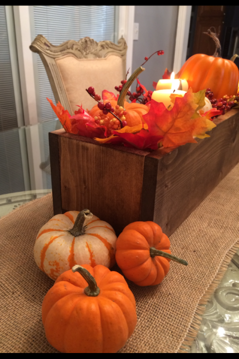 Close up of corner of centerpiece box on dining table with leaves and pumpkins