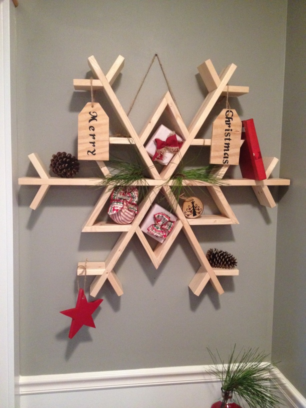 Wooden snowflake shelf decorated and hanging on wall