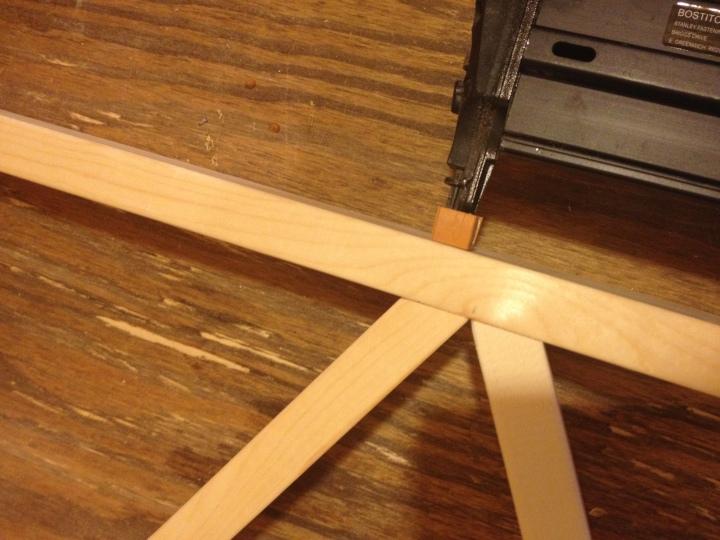 Close up of installing main wall shelf frame together